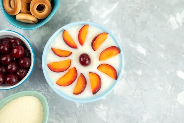 Dessert di vista superiore con i frutti affettati frutta dentro il piatto con la frutta fresca dei cracker dolci su bianco