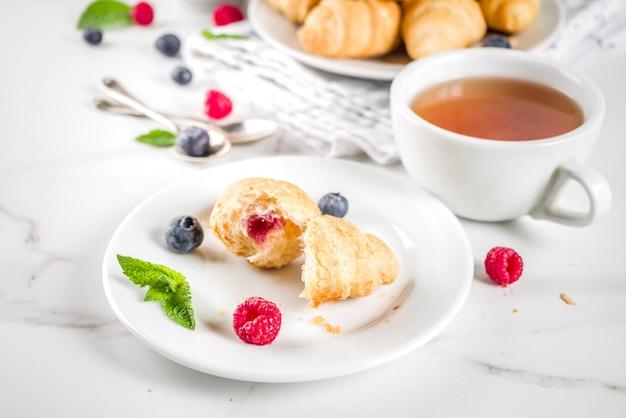 Dessert dolce, mini croissant al forno fatti in casa con marmellata di bacche, servito con tè, lamponi freschi, mirtilli e menta