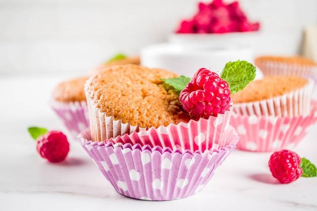 Dessert dolce, muffin al forno fatto in casa con marmellata di lamponi, servito con tè, lamponi freschi e menta