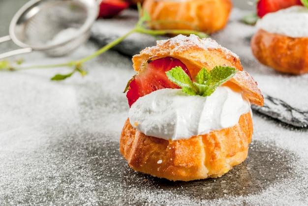 Dessert estivi cottura fatta in casa. profiteroles di torta con panna montata, fragole fresche, menta e spolverata di zucchero a velo. su un tavolo di pietra nera. copyspace