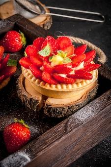 Dessert estivi e primaverili. tortini di torte fatte in casa con crema pasticcera e fragole