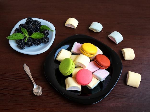 Dessert estivo e biscotti colorati: blackberry e foglie di menta su un piatto. caramella gommosa e molle, macarons su una tavola di legno