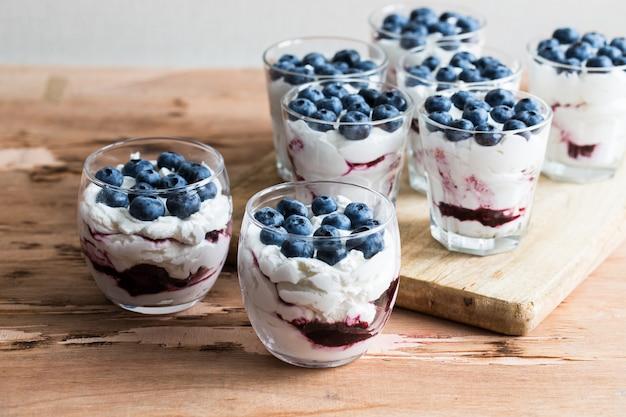 Dessert fatto in casa con yogurt e panna greci, marmellata di mirtilli e bacche di mirtillo fresche