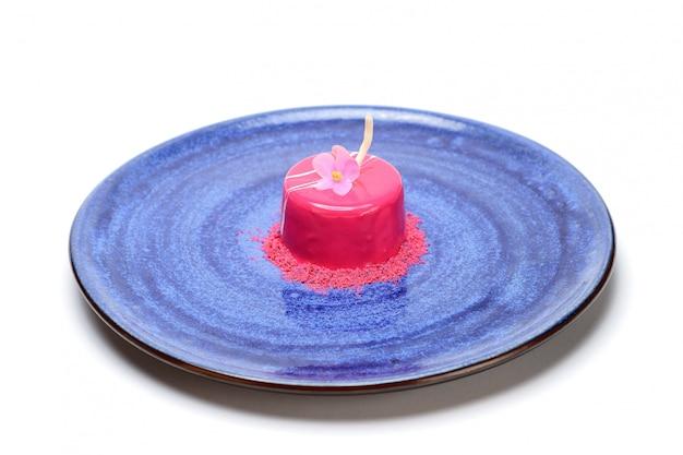 Dessert in smalto rosa decorato con un fiore. in un piatto blu