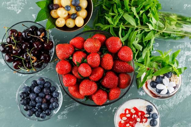 Dessert in vaso e calice con fragole, mirtilli, menta e ciliegia distesi su una superficie di gesso