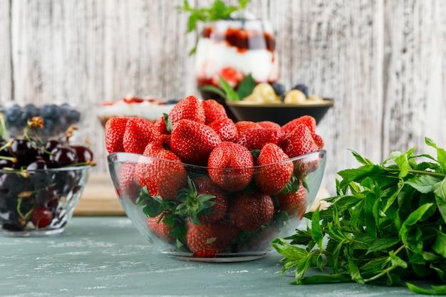 Dessert in vaso e calice con fragole, mirtilli, menta, vista laterale di ciliegie su gesso e superficie sgangherata