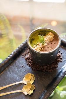 Dessert messo in una piccola pentola nera decorata con caffè macinato