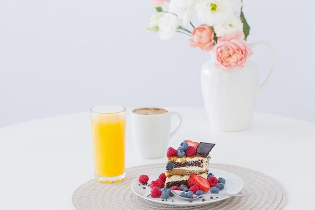 Dessert sano con differenti bacche su superficie bianca