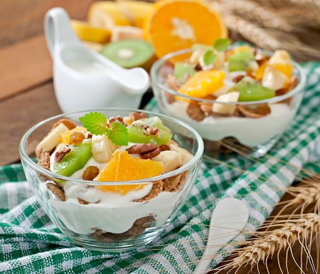 Dessert sano con muesli e frutta in una ciotola di vetro sul tavolo