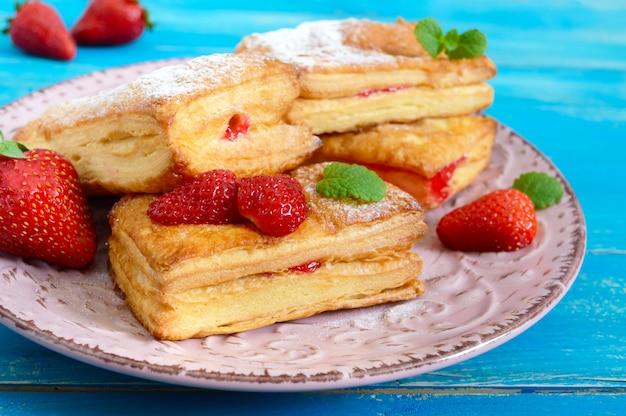 Dessert saporito dolce della pasta sfoglia su un piatto su un fondo di legno. deliziosi biscotti fatti in casa con marmellata di fragole, bacche e zucchero in polvere