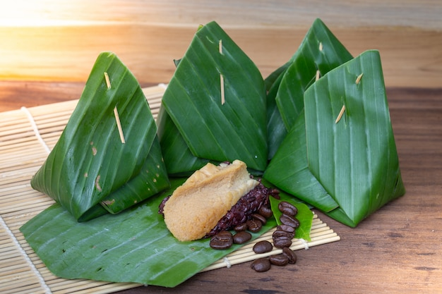 Dessert tailandese del riso appiccicoso del nero della crema sulla foglia della banana
