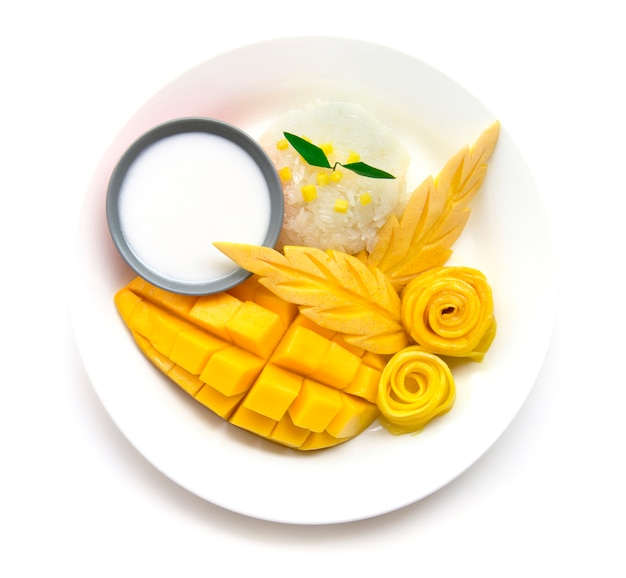 Dessert tailandese, mango con la vista superiore del latte di cocco dolce del riso appiccicoso isolata su fondo bianco