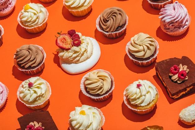 Dessert variopinti che mettono su fondo arancio.