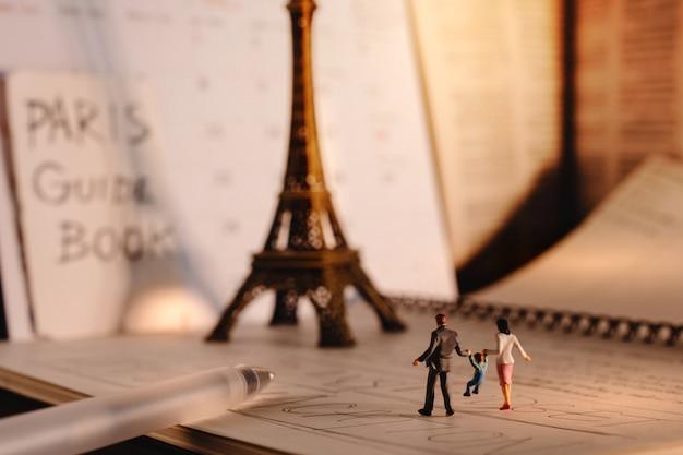 Destinazione da sogno per le vacanze. viaggia a parigi, in francia. una famiglia di turisti in miniatura che cammina alla torre eiffel e al calendario. tono caldo. stile vintage