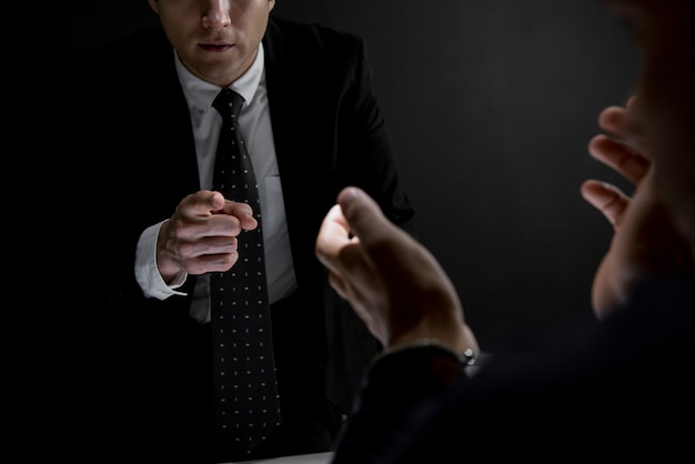Detective che indica la mano all'uomo criminale nella stanza di interrogatorio scuro