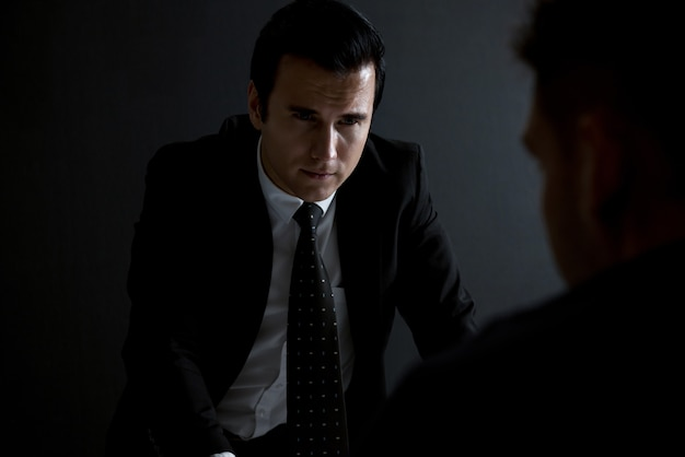 Detective che intervista il sospetto nella stanza degli interrogatori