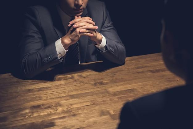 Detective che intervista un sospetto in una stanza buia