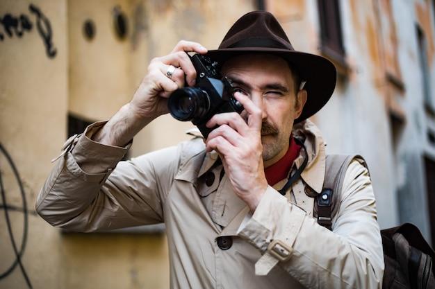 Detective che scatta foto in una baraccopoli con la sua macchina fotografica vintage
