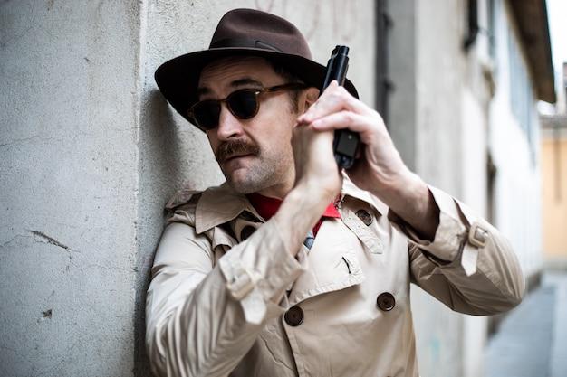 Detective che si copre e mira con la sua pistola
