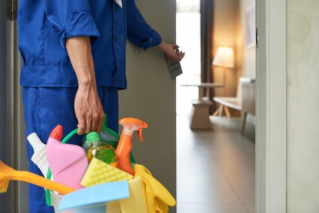 Detergente irriconoscibile che cammina nella camera d'albergo con strumenti e detergenti