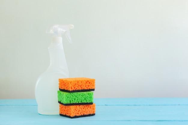Detergente spray per bottiglie bianco e spugna pulita su un tavolo.