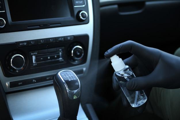 Detergere l'interno dell'auto e spruzzare con liquido disinfettante. disinfezione del volante e delle maniglie dell'auto. coronavirus, protezione covid-19 veicolo disinfettante all'interno,