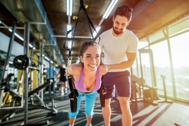 Determina un giovane personal trainer forte che aiuta la sua cliente a eseguire correttamente gli esercizi trx. il cliente sembra felice e soddisfatto.