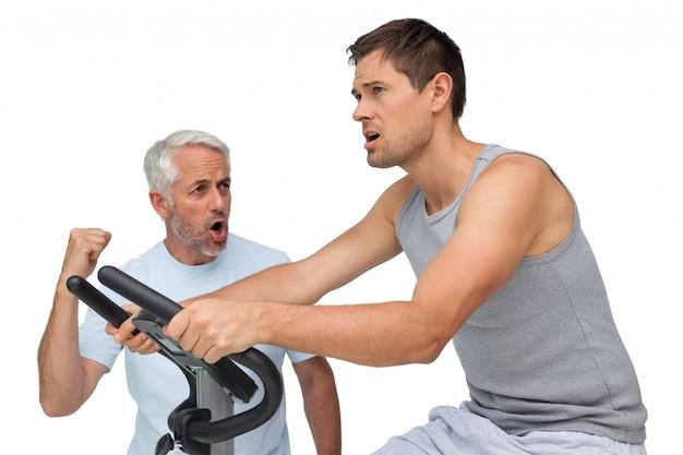 Determinato giovane sulla cyclette con trainer