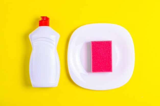 Detersivo per piatti, piatto e spugna rosa