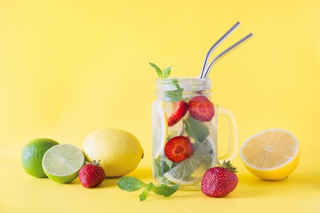 Detox acqua, limonata o mojito con limone, lime, fragola in barattolo su giallo