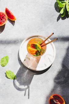 Detox acqua sul bicchiere con cannucce cocktail con arance rosse, foglie di menta