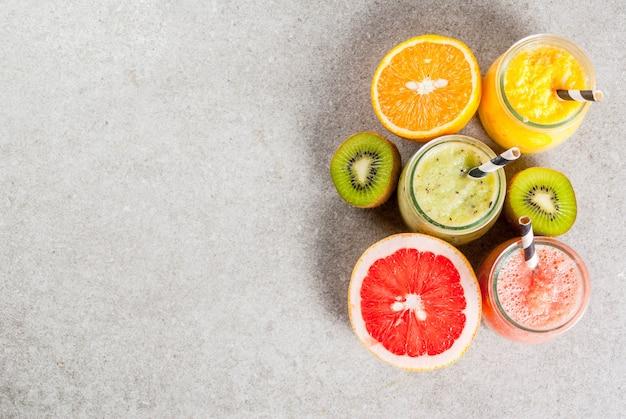 Detox bevande dietetiche biologiche, frullati tropicali fatti in casa - kiwi, arancia, pompelmo, in vasetti porzionati, con ingredienti, su un tavolo di pietra grigia. copia spazio vista dall'alto