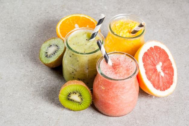 Detox bevande dietetiche biologiche, frullati tropicali fatti in casa - kiwi, arancia, pompelmo, in vasetti porzionati, con ingredienti, su un tavolo di pietra grigia. copyspace