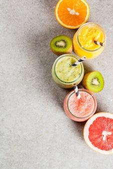 Detox bevande dietetiche biologiche, frullati tropicali fatti in casa - kiwi, arancia, pompelmo, in vasetti porzionati, con ingredienti, su un tavolo di pietra grigia. vista dall'alto di copyspace