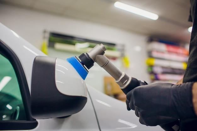Dettagli auto - lavoratore con lucidatrice orbitale nell'officina riparazioni auto. lucidatura a specchio per auto. messa a fuoco selettiva.