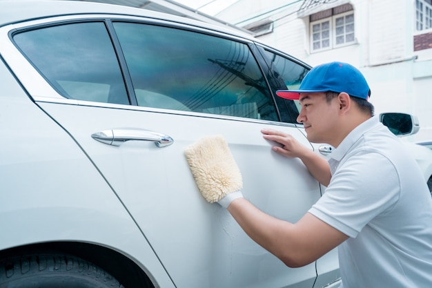Dettagli auto, uomo in uniforme blu pulire una macchina bianca in mano in possesso di una microfibra lavaggio auto di grandi dimensioni.