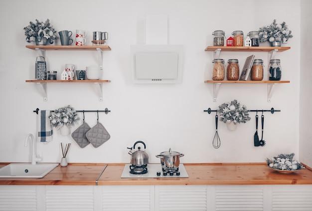 Dettagli degli interni della moderna cucina elegante bianca con elementi in legno in un appartamento in stile scandinavo