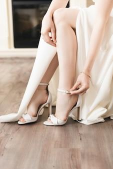 Dettagli del giorno del matrimonio. la sposa indossa scarpe da sposa