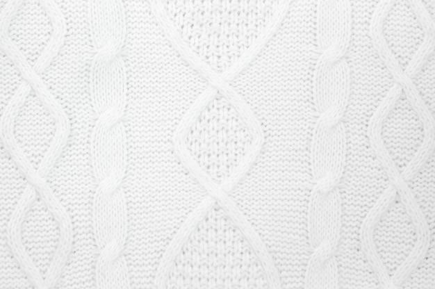 Dettagli del maglione di inverno tricottato bianco come fondo.
