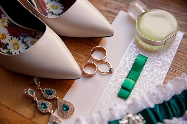 Dettagli del matrimonio. fedi nuziali, anello di fidanzamento, gioielli da sposa, giarrettiera e bottiglia di profumo su invito di nozze vicino a scarpe da sposa con i tacchi alti