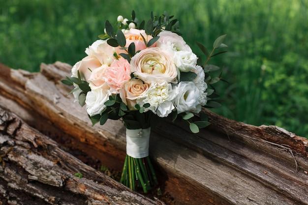 Dettagli della mattina del giorno del matrimonio. un delicato bouquet da sposa di rose e pioni bianchi e rosa. bellissimo bouquet da sposa all'aperto