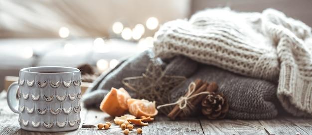 Dettagli della natura morta nel soggiorno interno della casa. bella tazza di tè con mandarini e maglioni su fondo in legno. accogliente concetto autunno-inverno