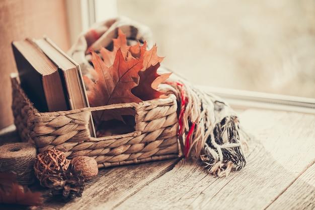 Dettagli della natura morta sulla finestra. canestro dei libri e delle foglie di autunno su fondo di legno.