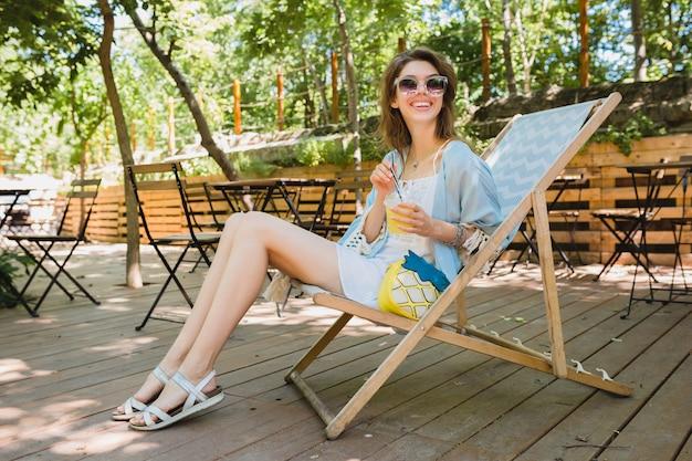 Dettagli di giovane donna seduta in una sedia a sdraio in abito di moda estiva, abito bianco, mantello blu, borsa gialla, bere limonata, accessori eleganti, gambe lunghe e sottili in sandali