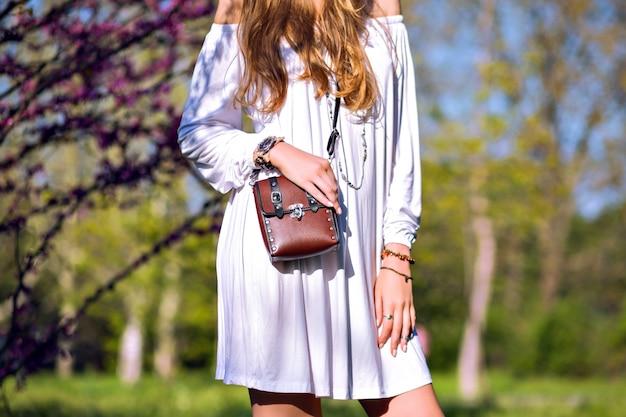 Dettagli di moda all'aperto di primavera, donna in posa al parco fiorito della città