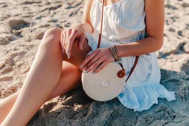 Dettagli di moda di close-up di donna in abito bianco con stile estivo borsa borsa di paglia su accessori da spiaggia