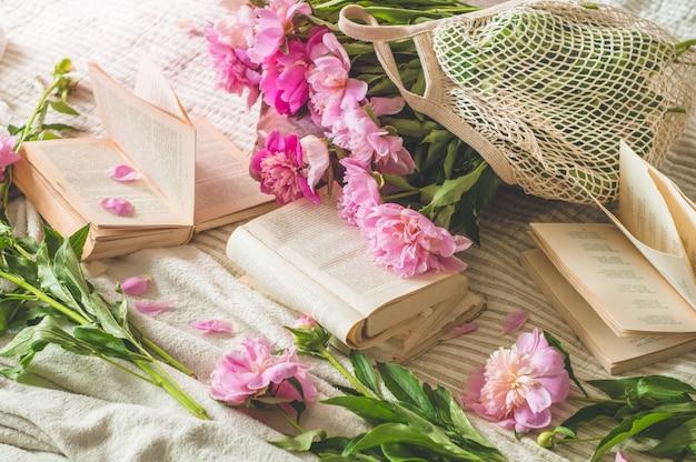 Dettagli di natura morta nell'interno domestico del salone. tazza di tè con fiori di pioni e decorazioni di primavera sui libri. leggi, riposa. concetto di primavera accogliente.