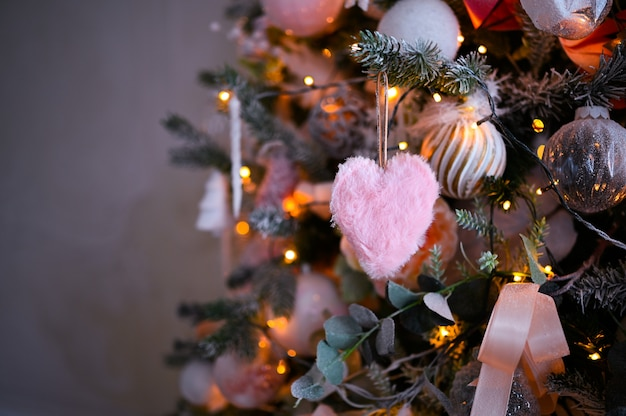 Dettagli di un albero di natale decorato in morbidi colori rosa con soffice cuore rosa.