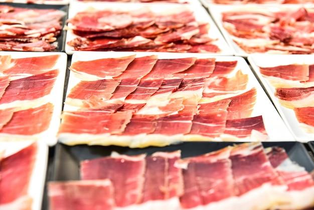 Dettaglia vari piatti di prosciutto serrano tagliato durante un evento.