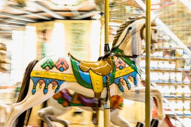 Dettaglio cavallo nostalgico di carosello di filatura con sfocature di luce durante la notte